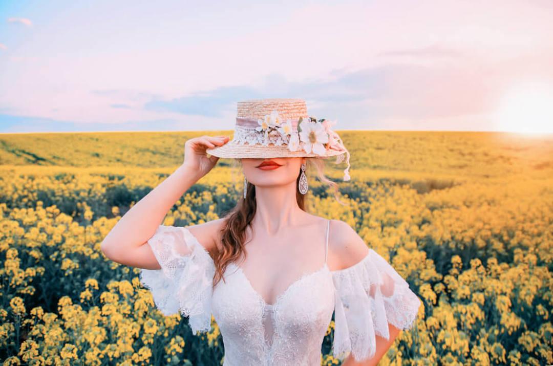 白いドレスと帽子を身に纏った女性