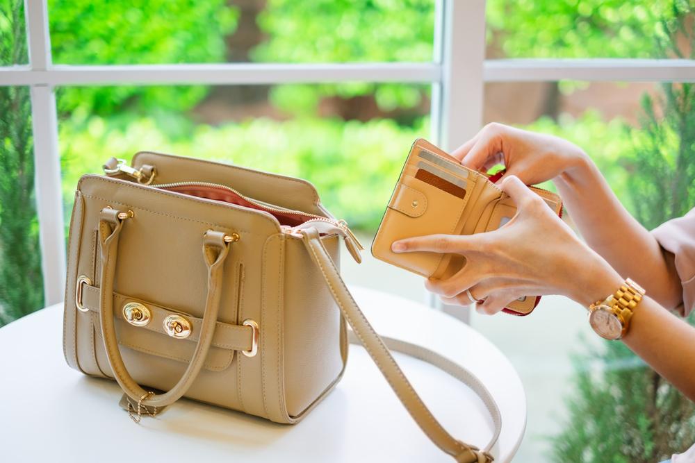 置かれたバッグと財布を使う女性