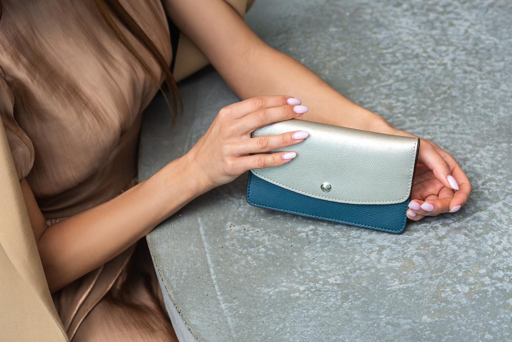 バイカラーの長財布を持つ女性