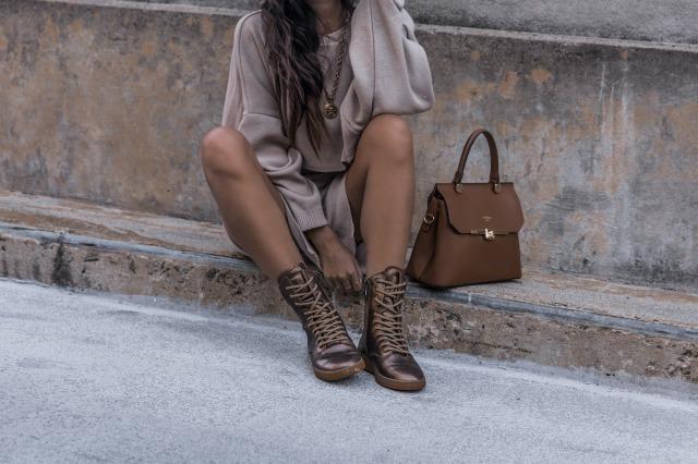 バッグを横に置いて道に座る女性