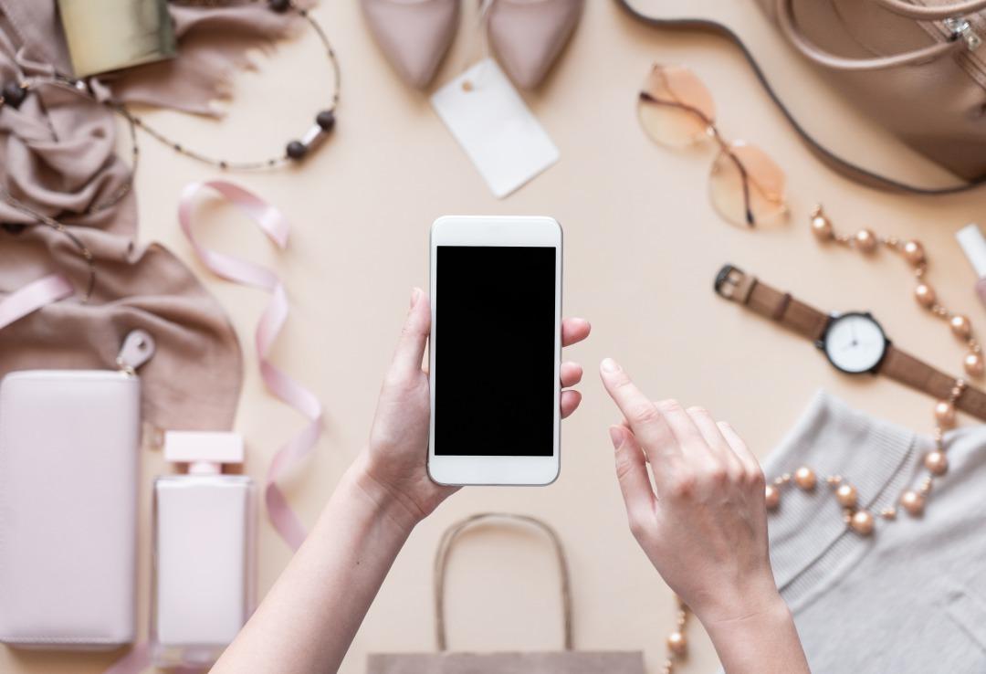 ファッションアイテムを背景にスマートフォンを操作している様子