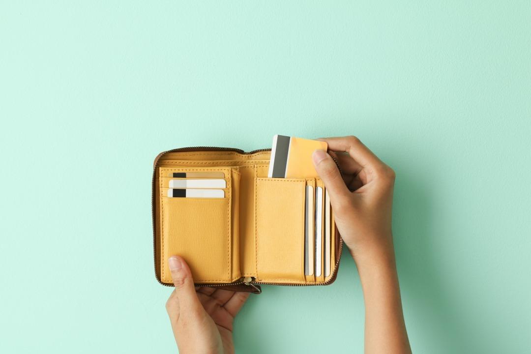 緑を背景に財布からカードを出している様子