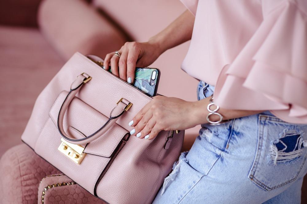 ピンクのトートバッグにスマホを入れる女性