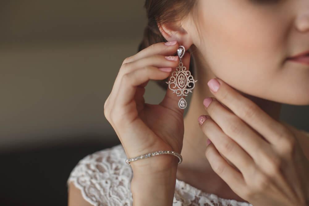 エレガントなイヤリングを付けるドレスの女性