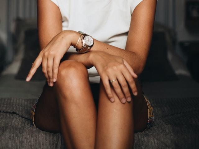売れ時計を着けた時計をクロスさせ座る女性