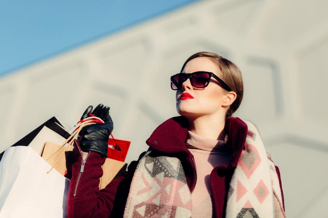 買い物袋を持ち満足げな女性
