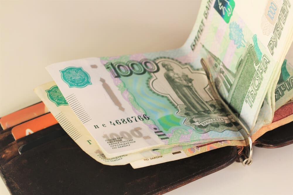 外国の紙幣が挟まれたレザー製のマネークリップ