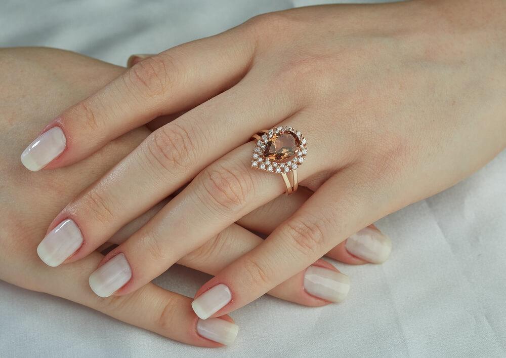 大ぶりのトパーズの指輪を付けた女性の手