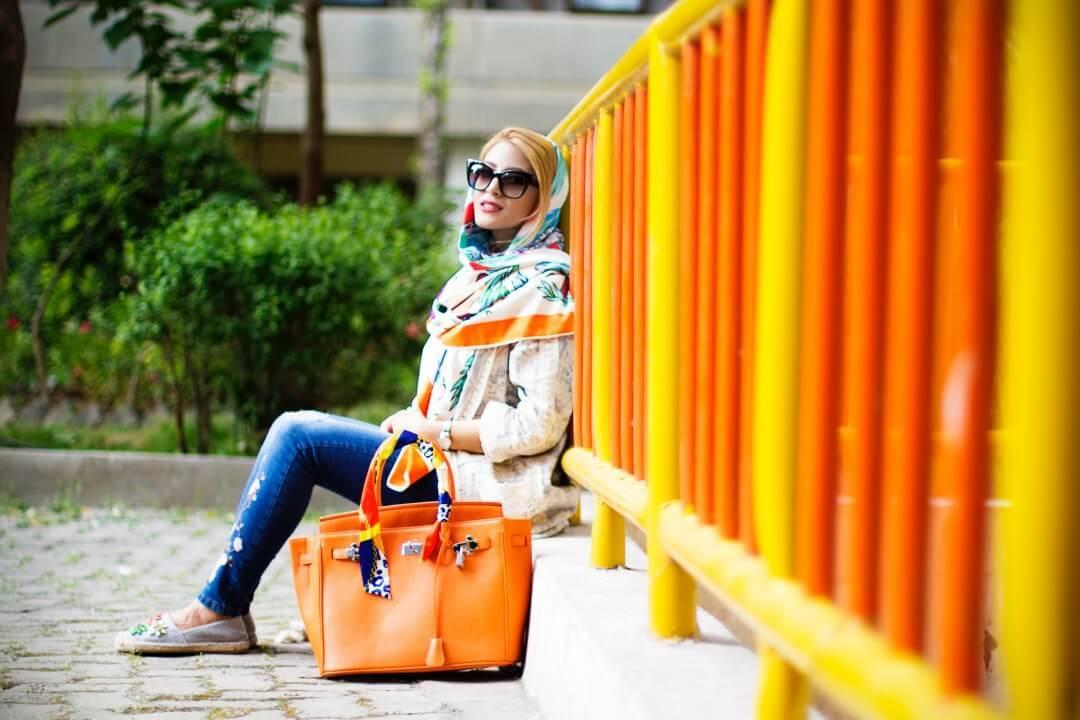 オレンジ色の柵にもたれかかり座る女性