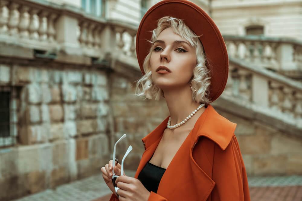 オレンジコートとパールネックレスを身につけた女性