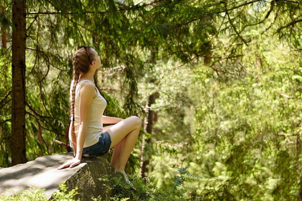 山の中で石に座る女性