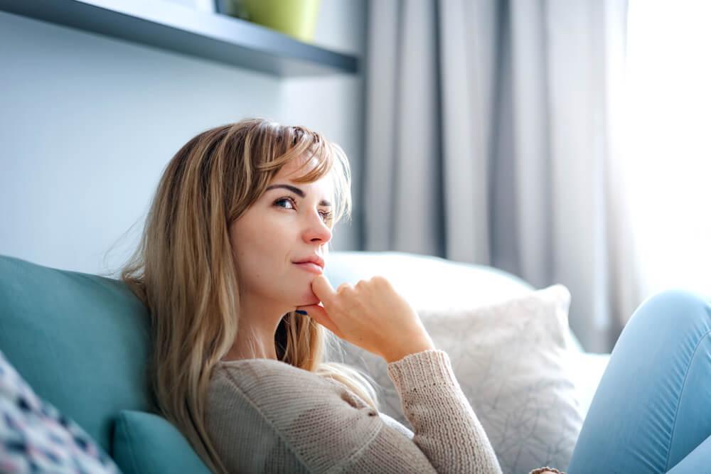 ソファに座って考え事をする女性
