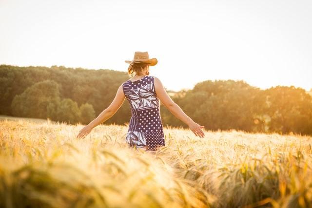 草原で両手を開くワンピの女性の後ろ姿