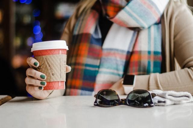 コーヒー片手にポーズを取るマフラーの女性
