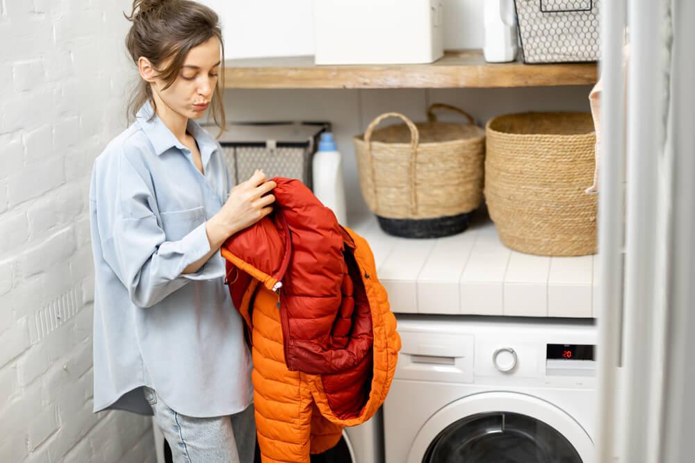 ダウンコートの洗濯表示を確認する女性
