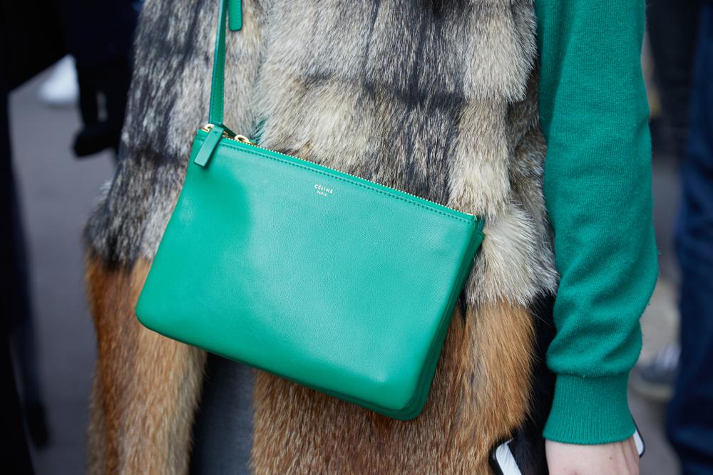 グリーンのトリオバッグを身に着ける女性