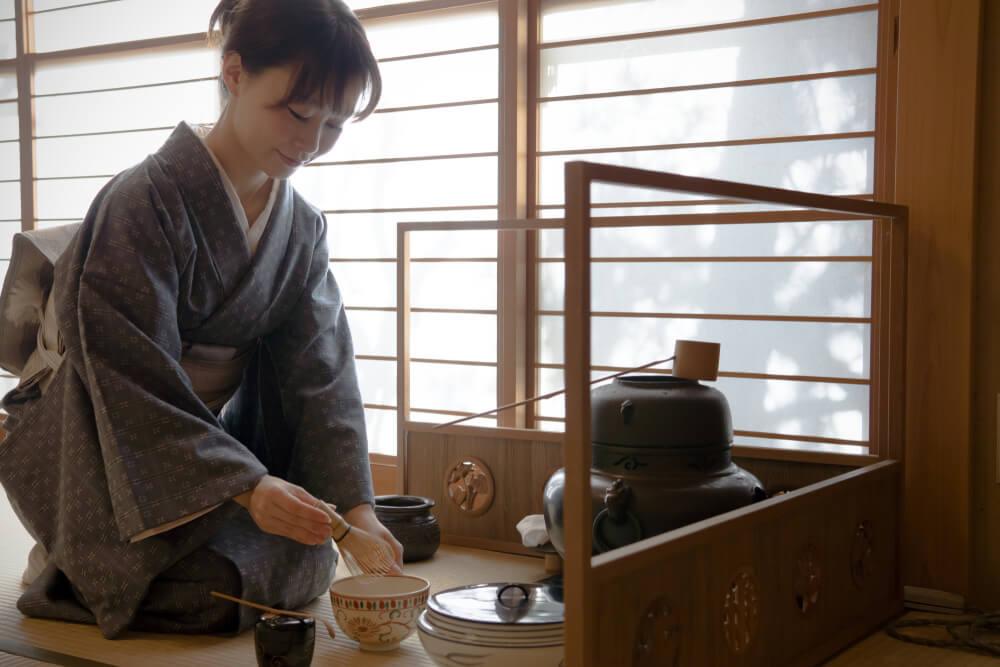茶道の稽古をする着物女性