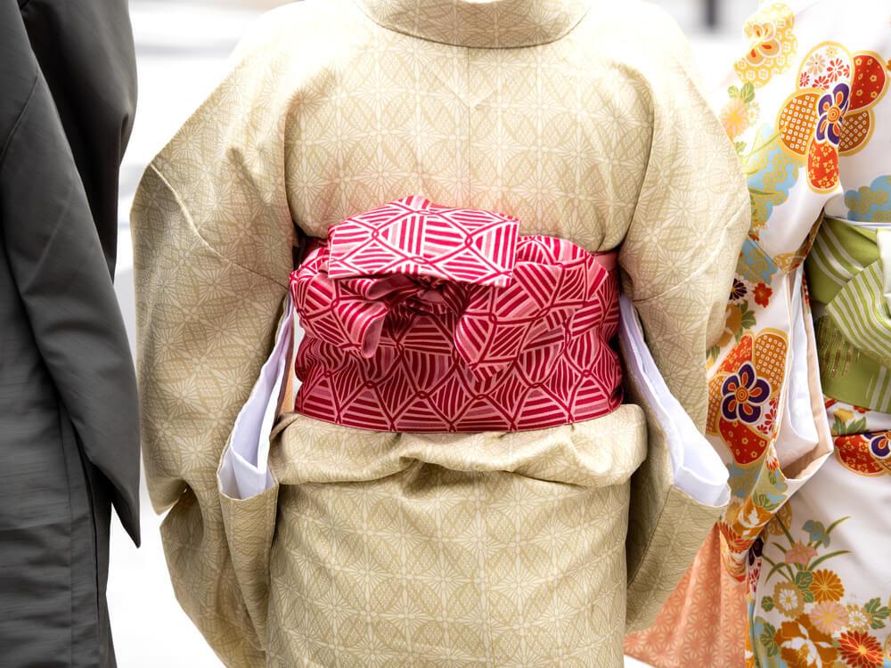 ベージュの着物に赤い帯を締めた女性と並ぶ着物を着た人々