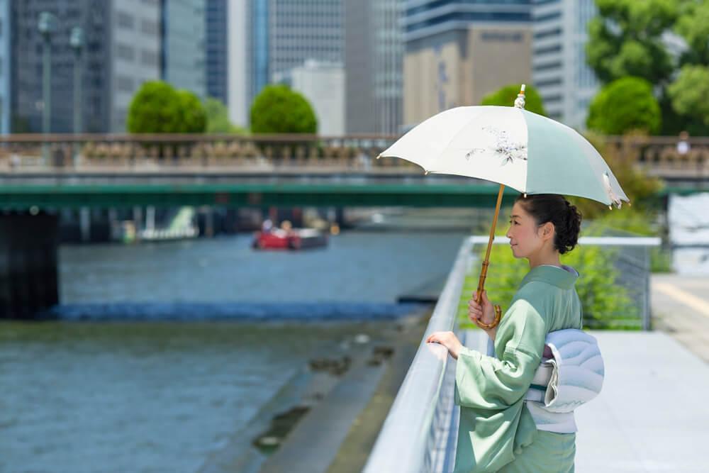 川辺で日傘をさして佇む着物女性