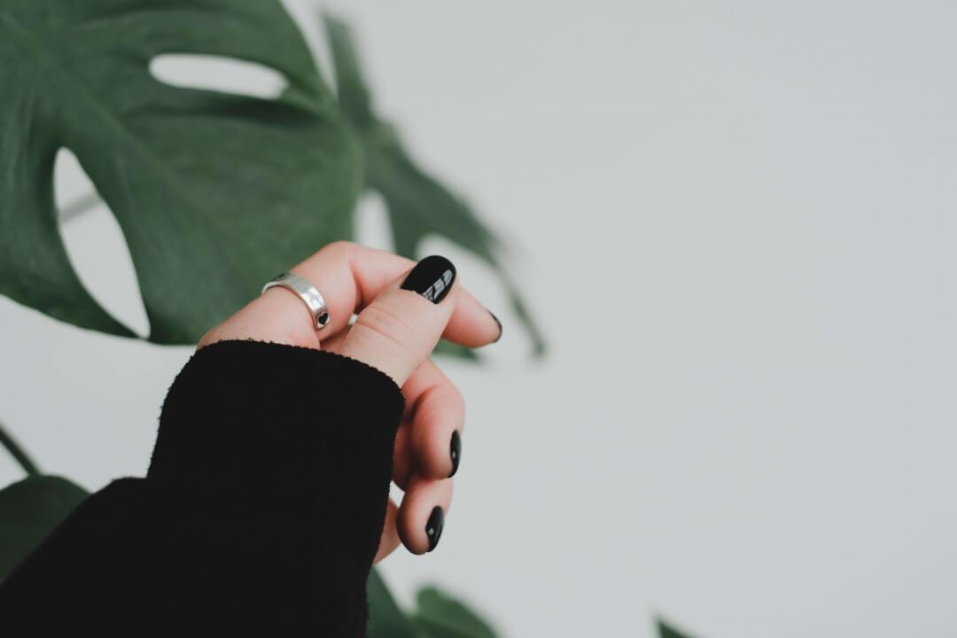 シルバーリングと黒いネイルの手元