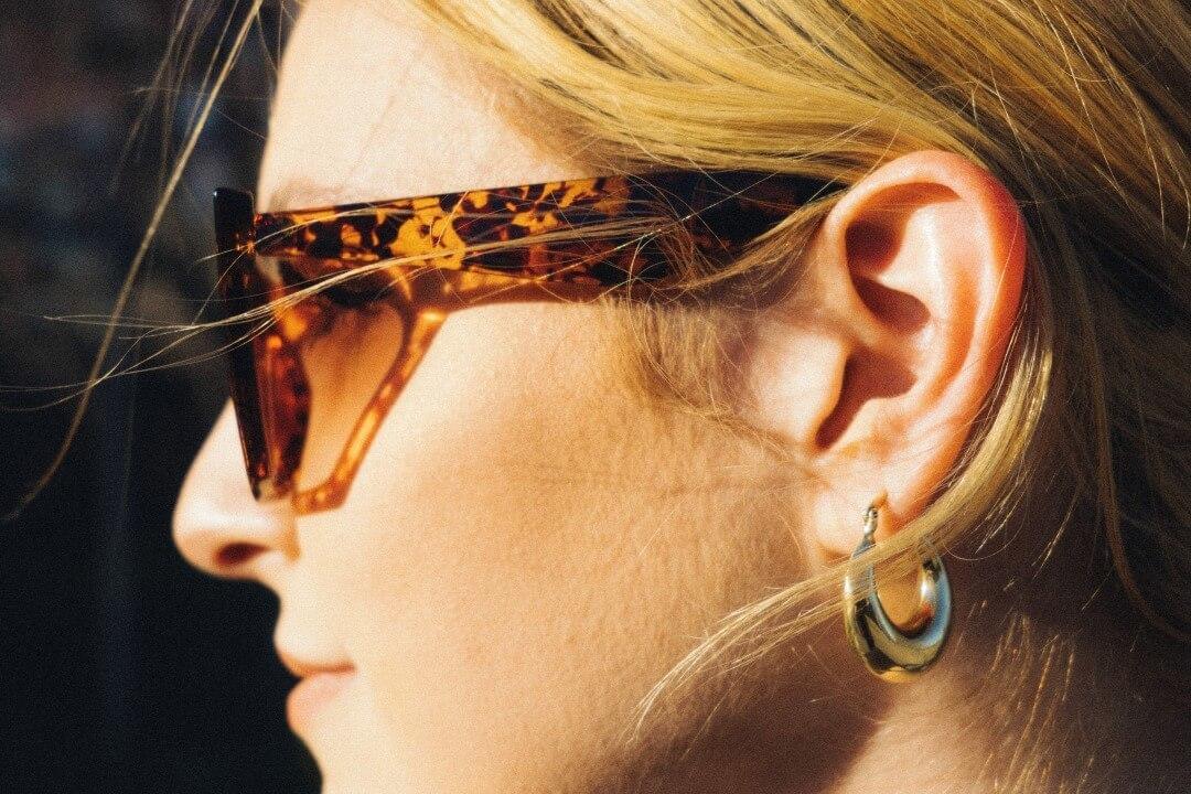 サングラスをかけた女性の耳元にシルバーピアス