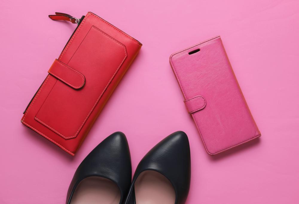 ピンク背景にスマホケースと財布とパンプス