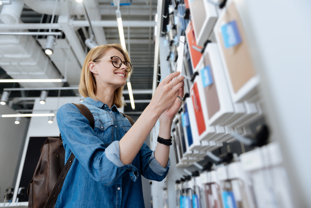 リユースショップでiPhoneケースを購入する女性
