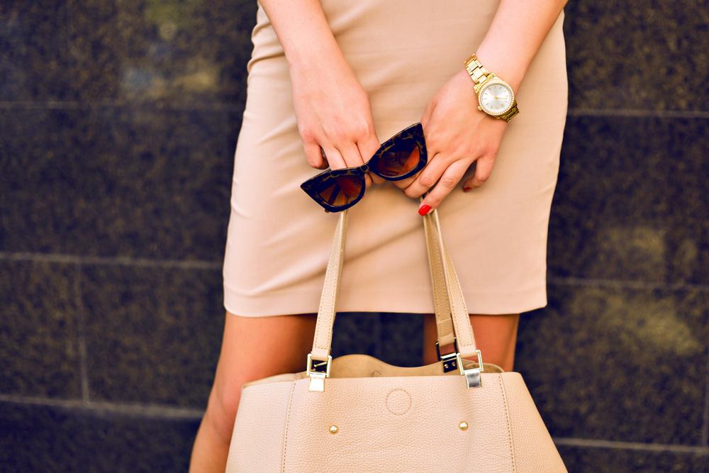 バッグ、サングラス、腕時計を身につけている女性