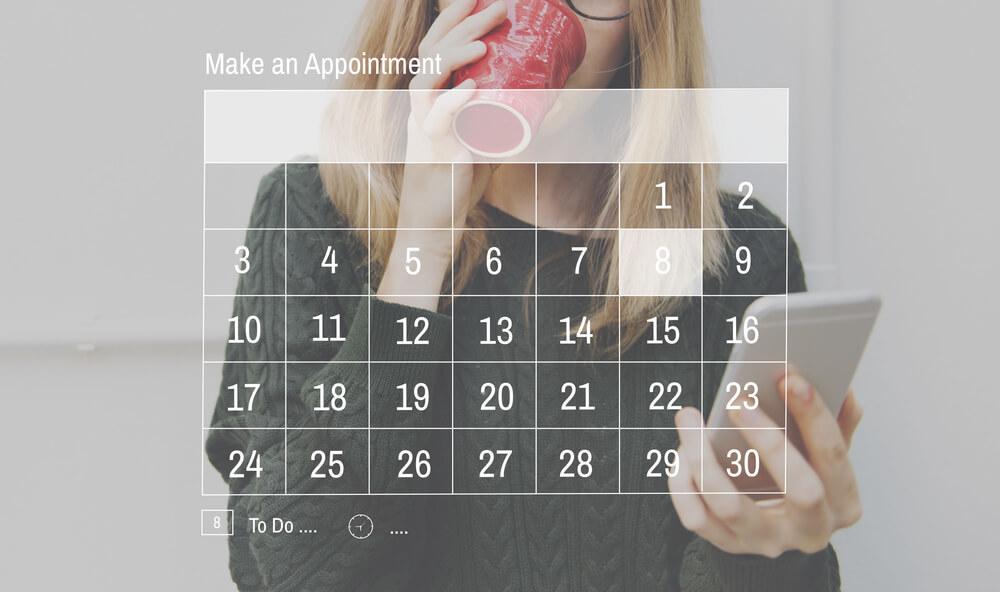 スマートフォンでカレンダーを見る女性