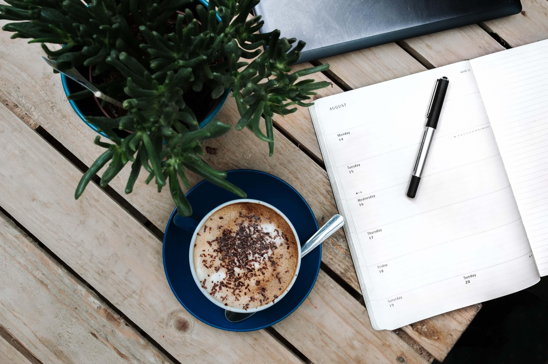 机の上の手帳とコーヒーと観葉植物
