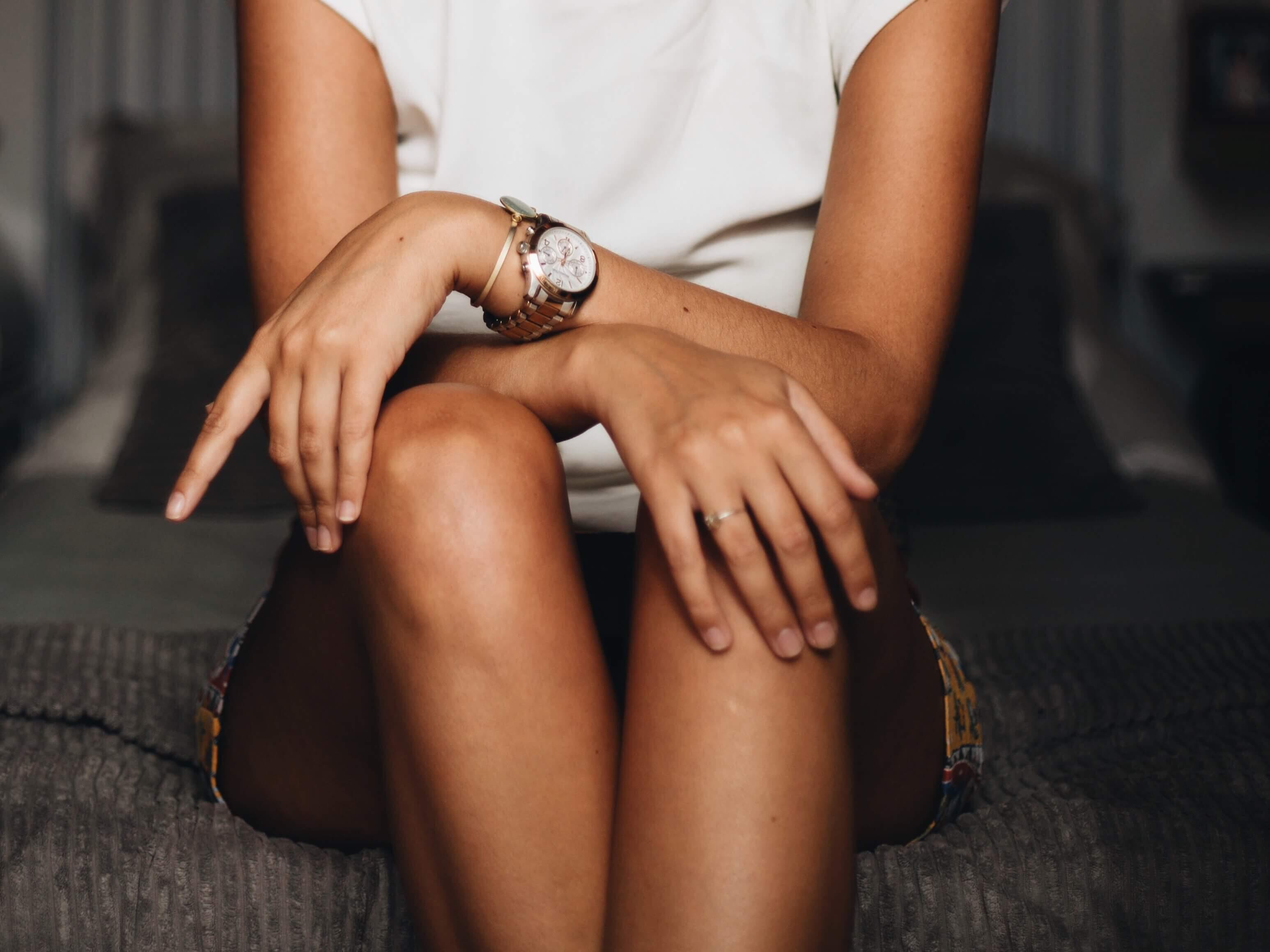 椅子に座って膝の上で手を組む女性