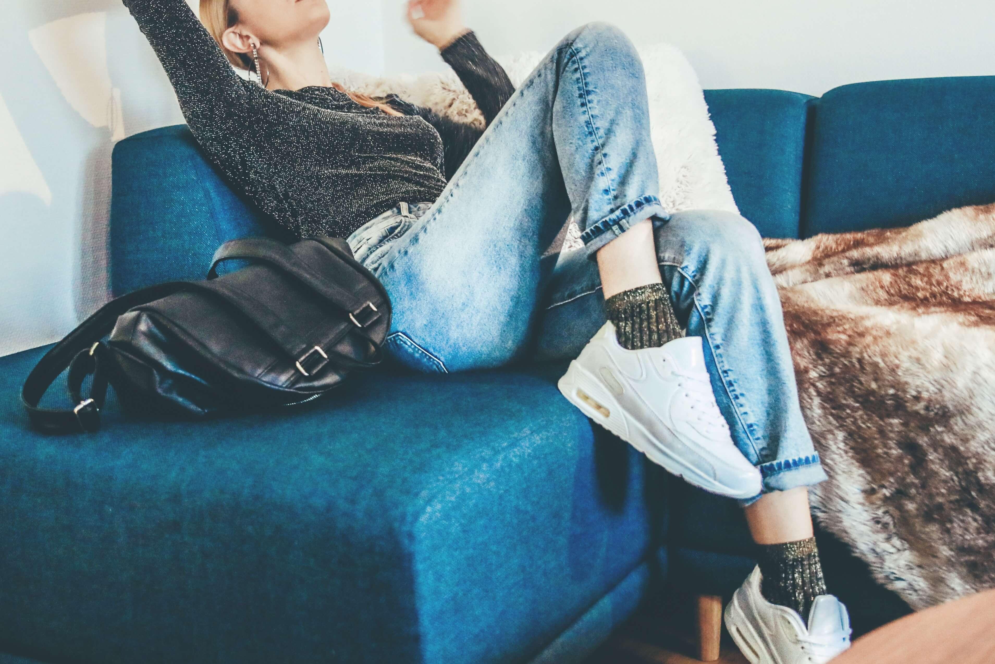 ソファで伸びをする女性