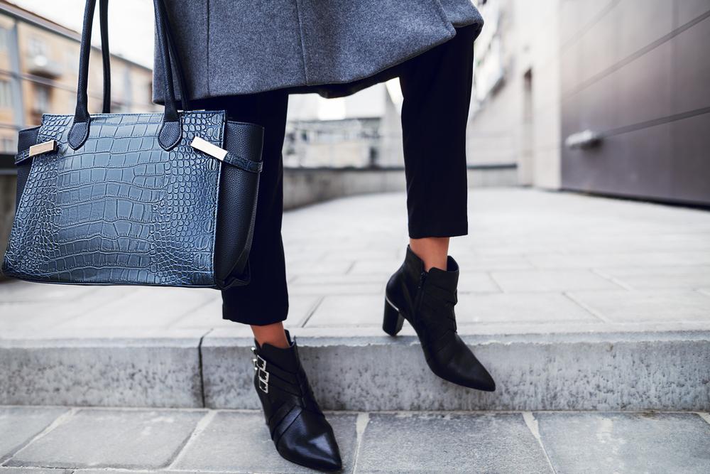 黒いアーガイル素材のバッグを手に持った女性の足元