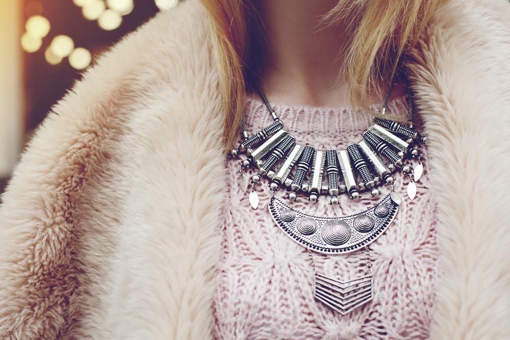 ファーコートを着て大ぶりなネックレスをつけた女性